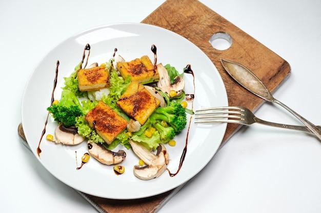 ブロッコリー豆腐のベジタリアン朝食。木の板の白い皿に