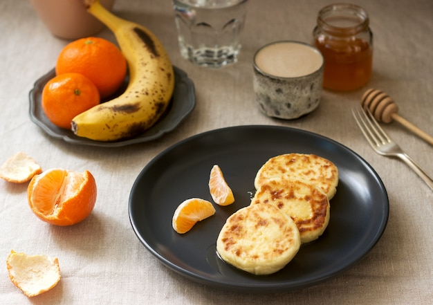 Vegetarian breakfast of quark pancakes with honey, fruit and coffee with milk. rustic style.