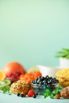 Vegetarian breakfast. soft boiled egg, oat flakes, nuts, fruits, berries, milk, yogurt, orange, banana, peach on blue background. healthy food diet.