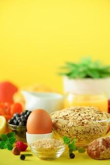 Vegetarian breakfast. soft boiled egg, oat flakes, nuts, fruits, berries, milk, yogurt, orange, banana, peach