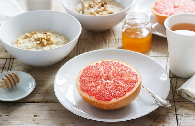 Vegetarian breakfast for two of oatmeal, baked grapefruit and tea. rustic style.