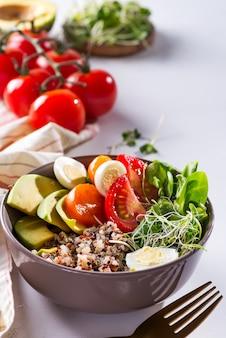 キノア、卵、マイクログリーンと野菜、白いテーブルにミント入りの緑茶、ベジタリアンブレックファースト、フラットレイアウト