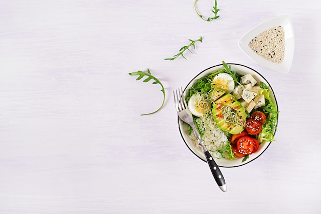 Vegetarian buddha bowl lunch with eggs, rice, tomato, avocado and blue cheese on table.
