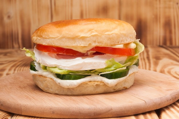 Vegetarian burger with cream cheese, cucumber and tomato