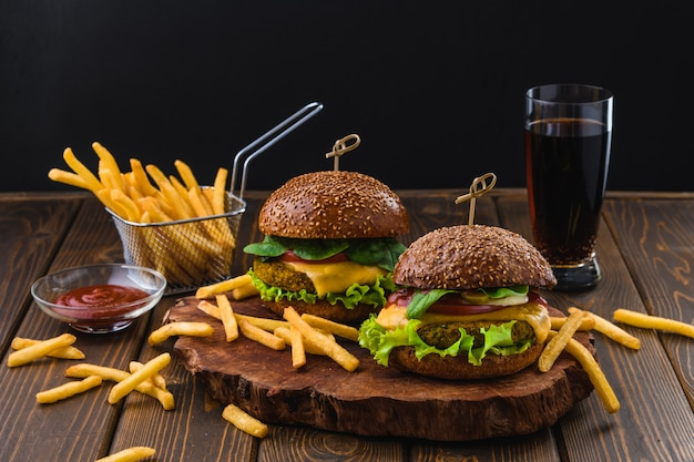 Vegetarian burger with fries and drink on wooden table