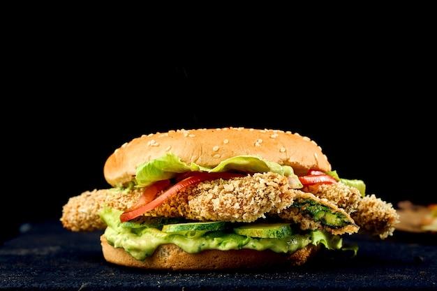 Вегетарианский бургер с соусом песто, огурцом, помидорами и спаржей в кляре на темном фоне .. крупным планом, выборочный фокус