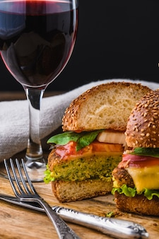 Vegetarian burger with wine on wooden table