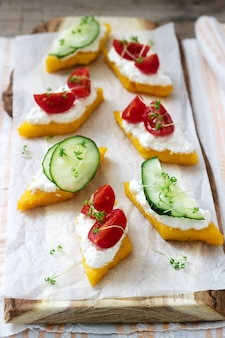 Vegetarian canapes from polenta with cheese, vegetables and cress. rustic style.