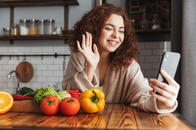 Вегетарианская кавказская женщина использует мобильный телефон во время приготовления салата из свежих овощей в интерьере кухни дома