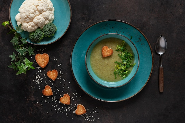 Vegetarian cauliflower, broccoli cream-soup with seeds heart shape crackers