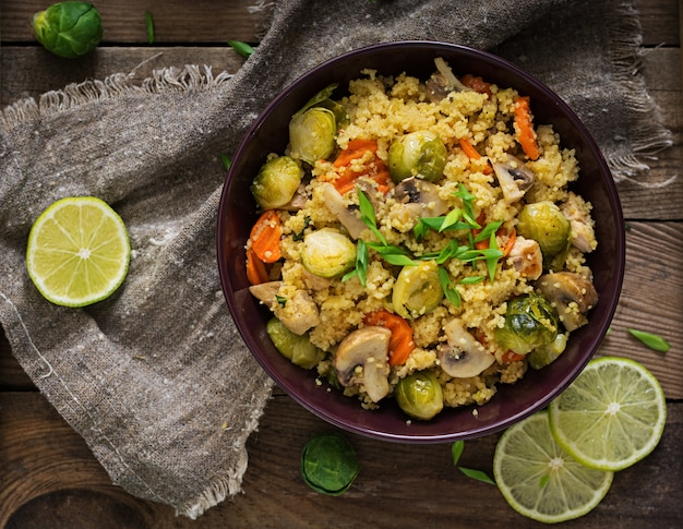 Vegetarian couscous salad with brussels sprouts, mushrooms, carrots and spices.