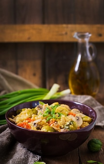 Vegetarian couscous salad with brussels sprouts, mushrooms, carrots and spices