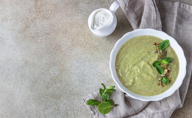민트와 씨앗을 곁들인 녹색 채소의 채식 크림 스프. 깨끗한 식사, 건강 식품 개념.