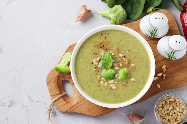Vegetarian cream soup with broccoli, spinach and zucchini in white bowl on gray background. top view. space for text