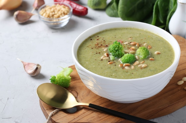 Vegetarian cream soup with broccoli, spinach and zucchini in white bowl on gray background.