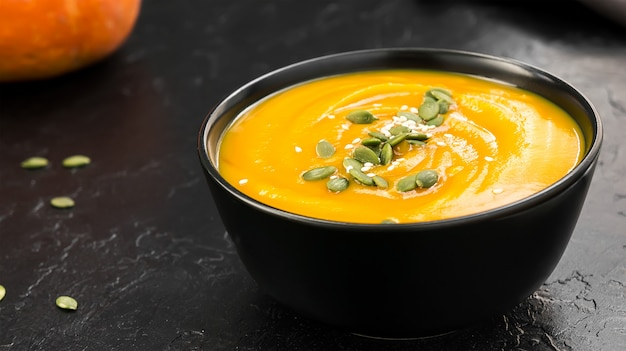 Vegetarian cream soup with pumpkin and seeds in black bowl