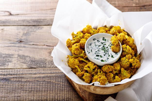 Vegetarian crispy cauliflower in wooden bowl with sauce and herbs on wooden background with copy space