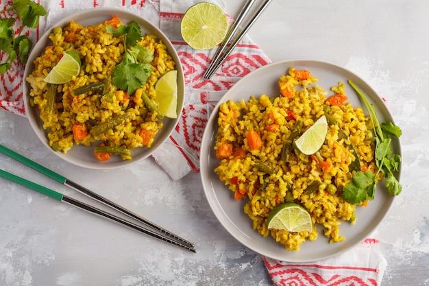 Вегетарианский рис карри с овощами и кокосовым кремом в серых тарелках. вид сверху, копия пространства, еда фон. концепция здорового веганского питания, детокс, овощная диета.