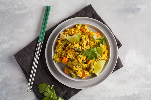 Vegetarian curry rice with vegetables in a gray plate. top view, copy space. healthy vegan food concept, detox, vegetable diet.