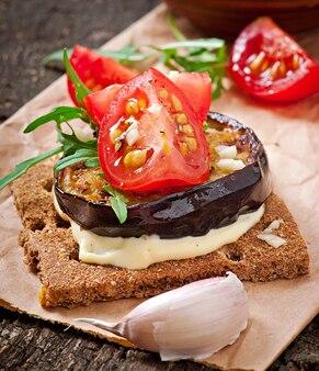 ベジタリアンダイエットクリスプブレッドサンドイッチ、ガーリッククリームチーズ、ローストしたナス、ルッコラ、古い木製のチェリートマト