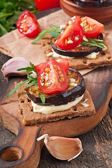 Vegetarian diet crispbread sandwiches with garlic cream cheese, roasted eggplant, arugula and cherry tomatoes on old wooden surface