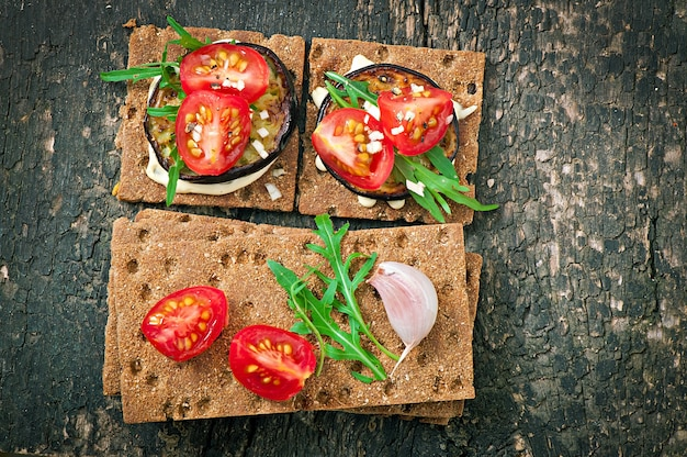 Vegetarian diet crispbread sandwiches with garlic cream cheese, roasted eggplant, arugula and cherry tomatoes on old wooden