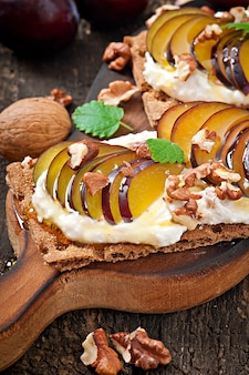 Vegetarian diet sandwiches crispbread with cottage cheese, plums, nuts and honey on old wooden