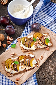 Vegetarian diet sandwiches crispbread with cottage cheese, plums, nuts and honey