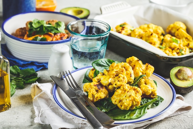 Vegetarian dining table. baked cauliflower salad with spinach, baked vegetables, vegan meatballs and avocado.