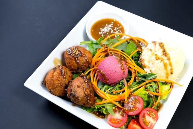 Вегетарианский ужин на тарелке на темном фоне.