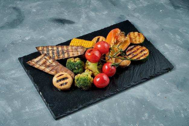 ベジタリアン料理-黒いスレート板に焼き野菜のセット。コンクリート表面