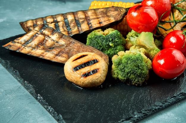 Вегетарианское блюдо - набор овощей гриль на черной грифельной доске на бетоне