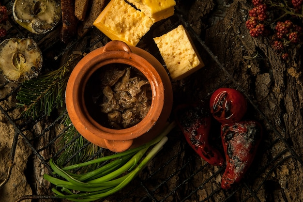 Вегетарианское блюдо в глиняном горшочке с запеченными овощами на мангале на фоне коры дерева