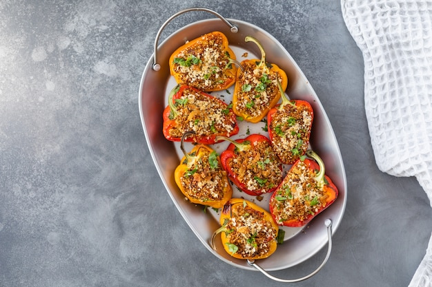 Vegetarian dish with peppers stuffed with quinoa, onion and tomato, sprinkled with walnuts