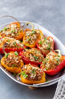 Vegetarian dish with peppers stuffed with quinoa, onion and tomato, sprinkled with walnuts.