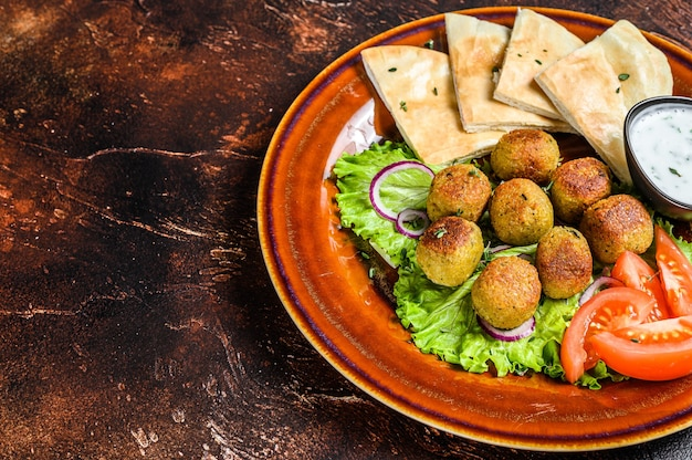 Vegetarian falafel with pita bread, fresh vegetables and sauce on a plate.