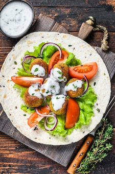 Vegetarian falafel with vegetables and tzatziki sauce on a tortilla bread