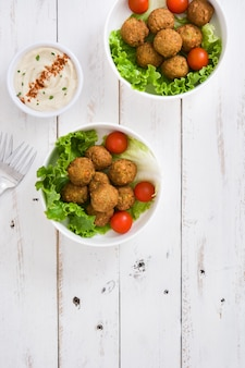 Vegetarian falafels in bowl and hummus on white wood top view