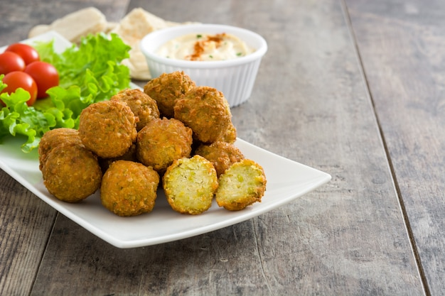 Vegetarian falafels and hummus on a rustic wooden table copy space