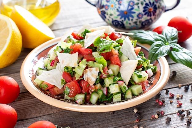 Вегетарианский салат фаттуш на деревянном столе. традиционный ближневосточный салат с поджаренным лавашем и овощами. ливанская кухня.