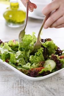 ベジタリアンフード。デトックス野菜サラダ-レタス、トマト、キュウリで味付けしたレモンオリーブグレービー。健康状態を監視する人のための料理
