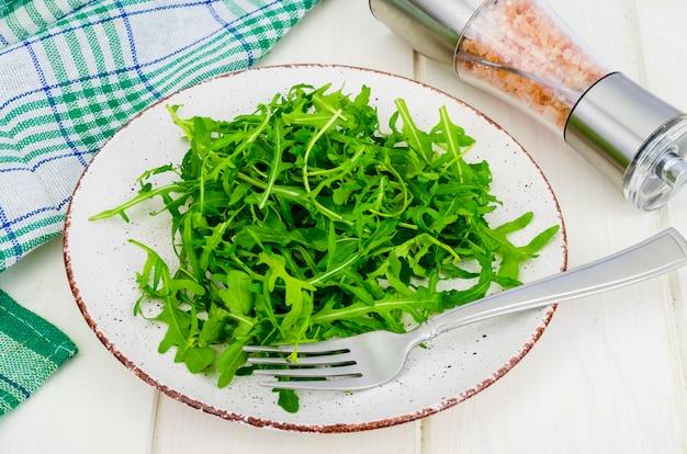 Vegetarian food. fresh green arugula on plate, white wooden