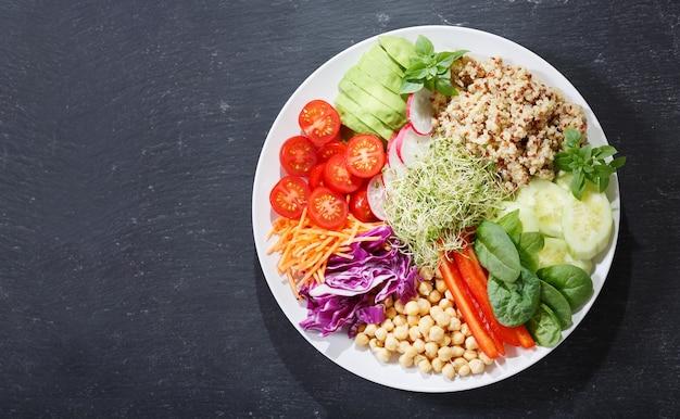 Вегетарианская пища. тарелка здорового салата с авокадо, киноа, помидорами, перцем, шпинатом, капустой, ростками и нутом, вид сверху