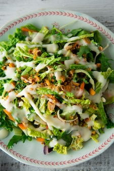 Vegetarian food with cabbage, eggs, greens, carrots and mayonnaise.