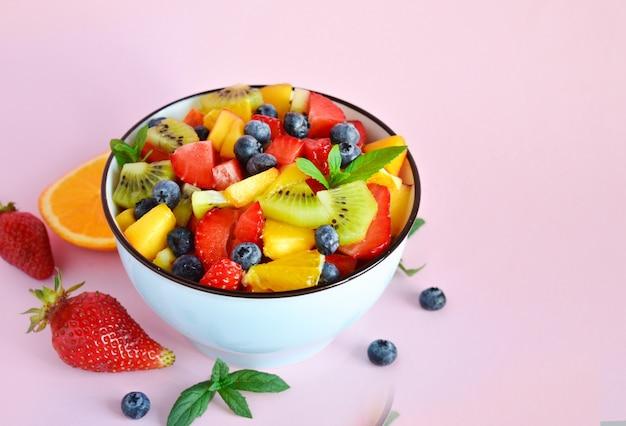 Вегетарианский свежий здоровый фруктовый салат на розовой таблице из разных фруктов.
