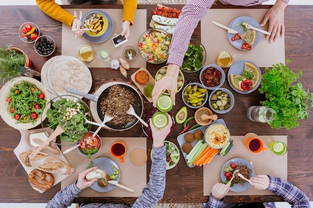木製のテーブルに座ってレモン水とグラスをチリンと菜食主義者の友人