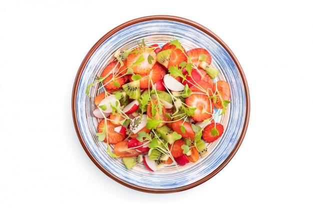 イチゴ、キウイ、トマト、白い背景で隔離のマイクログリーンスプラウトのベジタリアンフルーツと野菜のサラダ。トップビュー、クローズアップ。
