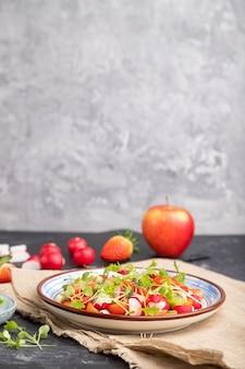 イチゴ、キウイ、トマト、黒と灰色の背景にマイクログリーンスプラウトのベジタリアンフルーツと野菜のサラダ。側面図、セレクティブフォーカス、コピースペース。
