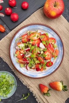 イチゴ、キウイ、トマト、黒緑色のコンクリートの背景に緑の芽のベジタリアンフルーツと野菜のサラダ。トップビュー、クローズアップ。