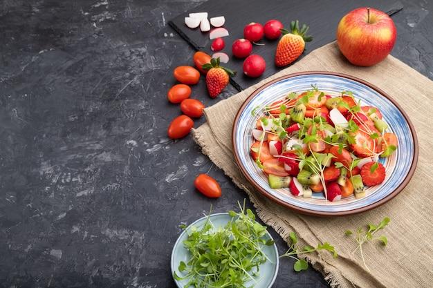 イチゴ、キウイ、トマト、黒緑色のコンクリートの背景に緑の芽のベジタリアンフルーツと野菜のサラダ。